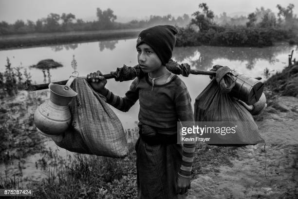COX'S BAZAR BANGLADESH NOVEMBER 02 A Rohingya Muslim refugee carries his belongings as he walks alone after crossing the border from Myanmar into...