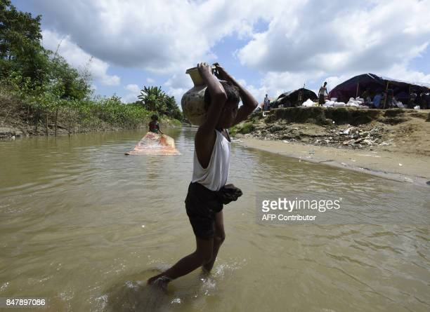 A Rohingya Muslim refugee carries water at Jalpatoli refugee camp in the 'no mans land' between Myanmar and Bangladesh in Gumdhum district on...