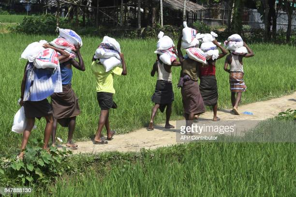 Rohingya Muslim refugee carry supplies through the Jalpatoli refugee camp in the 'no mans land' between Myanmar and Bangladesh in Gumdhum district on...