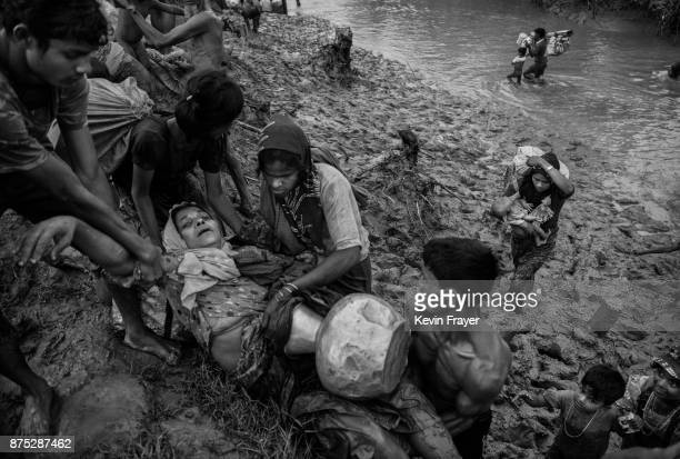 COX'S BAZAR BANGLADESH NOVEMBER 01 A Rohingya Muslim refugee is helped by others after collapsing after fleeing over the border from Myanmar into...