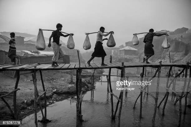 COX'S BAZAR BANGLADESH OCTOBER 27 Rohingya Muslim refugee men carry food aid across makeshift bamboo bridges on October 27 2017 at the Kutupalong...