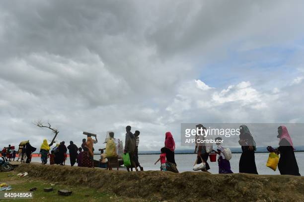 Rohingya Muslim refugees arrive from Myanmar after crossing the Naf river in the Bangladeshi town of Teknaf on September 12 2017 Some 370000 Rohingya...