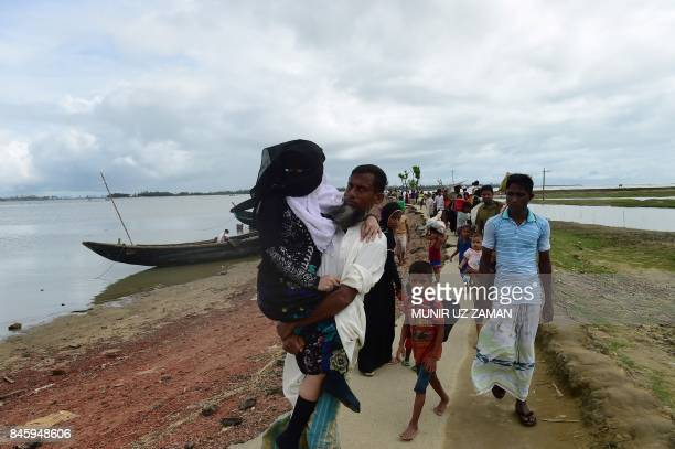 TOPSHOT Rohingya Muslim refugees carry an elderly relative as they arrive from Myanmar after crossing the Naf river in the Bangladeshi town of Teknaf...