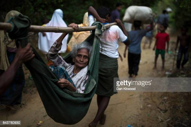 Rohingya Muslim refugees carry an elderly woman to a settlement after crossing the Myanmar Bangladesh border on September 07 2017 in Balukhali Bazar...