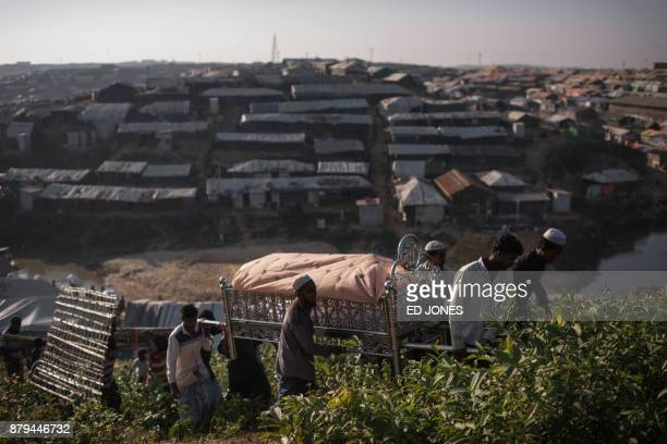 TOPSHOT Rohingya Muslim refugees carry the body of an elderly woman who died from an undiagnosed illness towards a gravesite on a hillside in the...