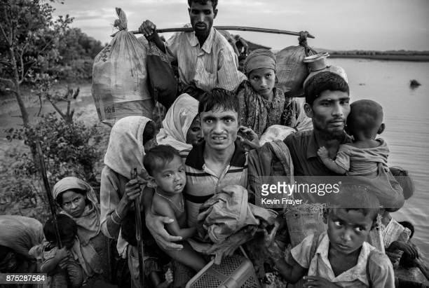 COX'S BAZAR BANGLADESH NOVEMBER 01 Rohingya Muslim refugees carry their belongings as they crowd on a berm while waiting to be allowed to proceed...