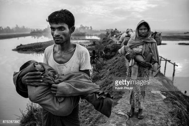 COX'S BAZAR BANGLADESH NOVEMBER 02 Rohingya Muslim refugees carry their children as they walk on an earthen berm after crossing the border from...