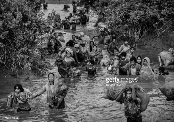 COX'S BAZAR BANGLADESH NOVEMBER 01 Rohingya Muslim refugees crowd a canal as they flee over the border from Myanmar into Bangladesh at the Naf River...