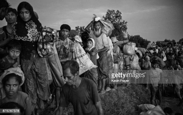 COX'S BAZAR BANGLADESH NOVEMBER 01 Rohingya Muslim refugees crowd on a berm as they wait to be allowed to proceed after fleeing over the border from...