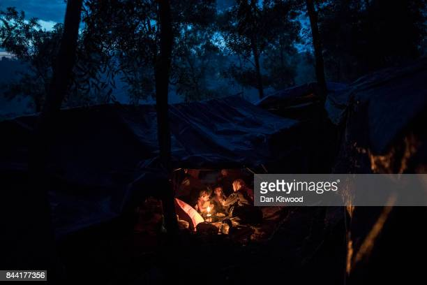 Rohingya Muslim refugees eat over a fire in a more established shelter in a refugee camp on September 08 2017 in Gundum Bangladesh Thousands of...