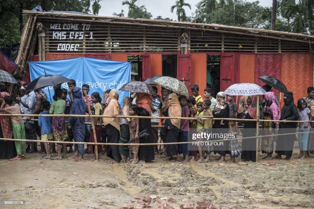Rohingya Muslim refugees line up for food distribution in the Kutupalong refugee camp in the Bangladesh's Ukhia district on September 28, 2017. The UN has drawn up a contingency plan to feed up to 700,000 Muslim Rohingya refugees from Myanmar after some 480,000 fled to Bangladesh over the past month and arrivals continue. A senior official from the UN's World Food Program (WFP) told AFP they were now prepared to provide massive food and other emergency aid if the influx continues in coming weeks. DUFOUR
