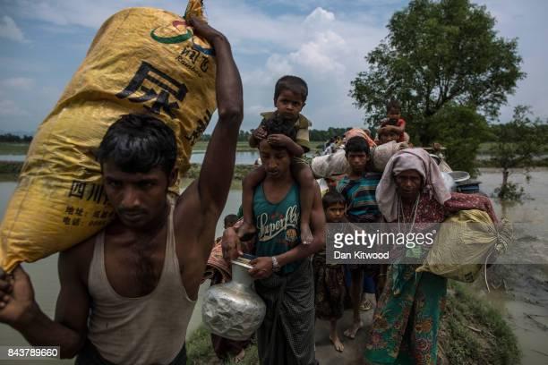 Rohingya Muslim refugees make their way into Bangladesh after crossing the Myanmar Bangladesh border on September 07 2017 in Whaikhyang Bangladesh...
