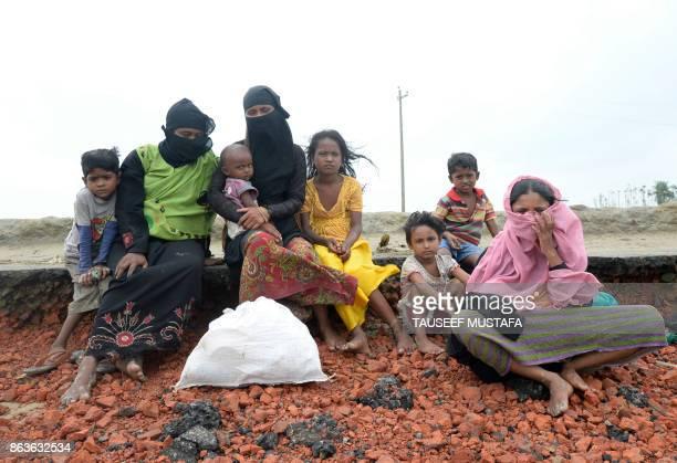 TOPSHOT Rohingya Muslim refugees rest after crossing into Bangladesh from Myanmar on Shah Porir Dwip Island near Teknaf on October 20 2017 Some...