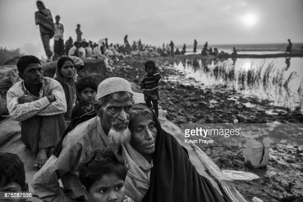 COX'S BAZAR BANGLADESH NOVEMBER 02 Rohingya Muslim refugees rest in the early morning as they sit on an earthen berm while waiting to proceed to...
