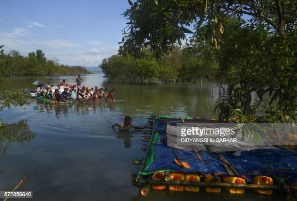 TOPSHOT Rohingya Muslim refugees sail a makeshift raft made from jerrycans and bamboo across the Naf River into Bangladesh at Sabrang Teknaf district...