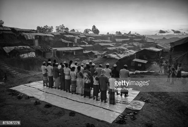 COX'S BAZAR BANGLADESH OCTOBER 22 Rohingya Muslim refugees stand as they pray at the site of a new mosque being built on October 22 2017 at the...