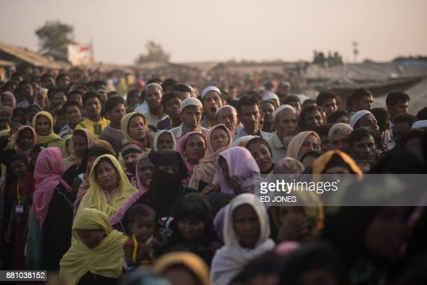Rohingya Muslim refugees wait to be called to recieve food aid of rice water and cooking oil in a relief centre at the Kutupalong refugee camp in...