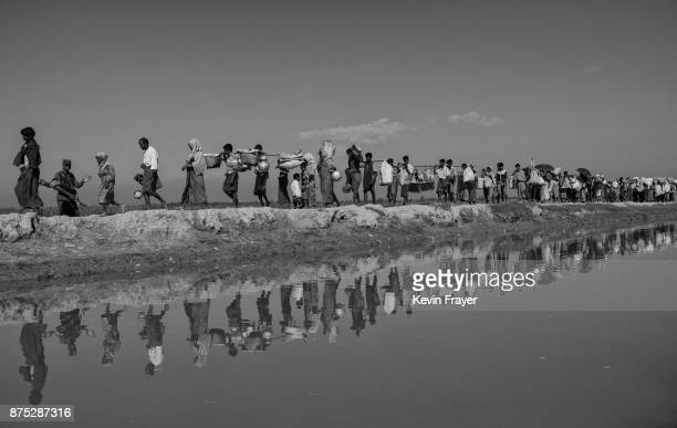 COX'S BAZAR BANGLADESH NOVEMBER 02 Rohingya Muslim refugees walk on an earthen berm as they proceed to camps after crossing the border from Myanmar...