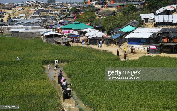 TOPSHOT Rohingya Muslim refugees walks through a paddy field to go to their camps after collecting relief materials at the Balukhali refugee camp in...