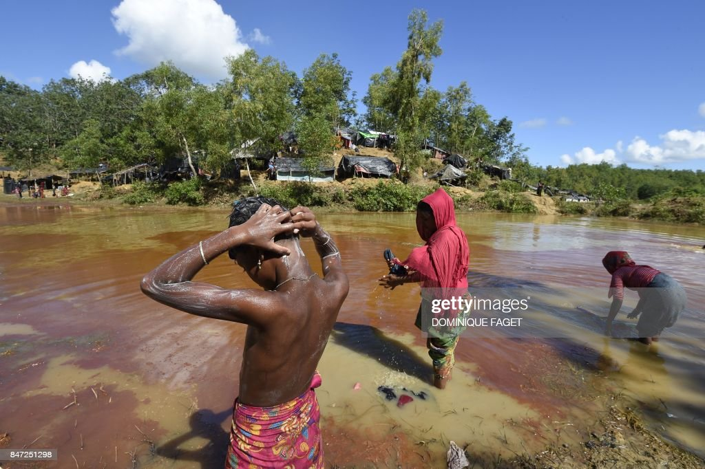 TOPSHOT - Rohingya Muslim refugees wash in a canal at Kutupalong refugee camp in Bangladesh's Cox's Bazar district on September 15, 2017. Bangladesh will use troops to deliver foreign aid to the bo...