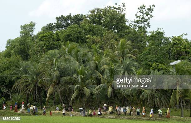 TOPSHOT Rohingya Muslim refugees who were stranded after leaving Myanmar walk from the 'noman's land' between Myanmar and Bangladesh into Palongkhali...