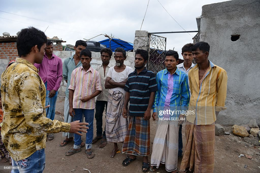 Rohingya Muslim Saddiq Hussain (L) talks to fellow refugees at their camps in the old city of Hyderabad on June 29, 2016. More than 1,200 Rohingya Muslims fleeing sectarian violence in Myanmar have settled in crammed quarters and makeshift shelters in the old city in Hyderabad, in the southern Indian state of Telangana. The Rohingyas have been described by the United Nations as one of the world's most persecuted minorities. They have fled Myanmar in their thousands in recent years as hardline monks and Buddhist nationalists fiercely oppose moves to recognise them as an official minority and insist on calling them 'Bengalis' -- shorthand for illegal migrants from the border with Bangladesh. / AFP / NOAH