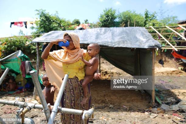 Rohingya Muslim woman fled from ongoing military operations in Myanmars Rakhine state drinks water supplied by local authority as she holds a child...