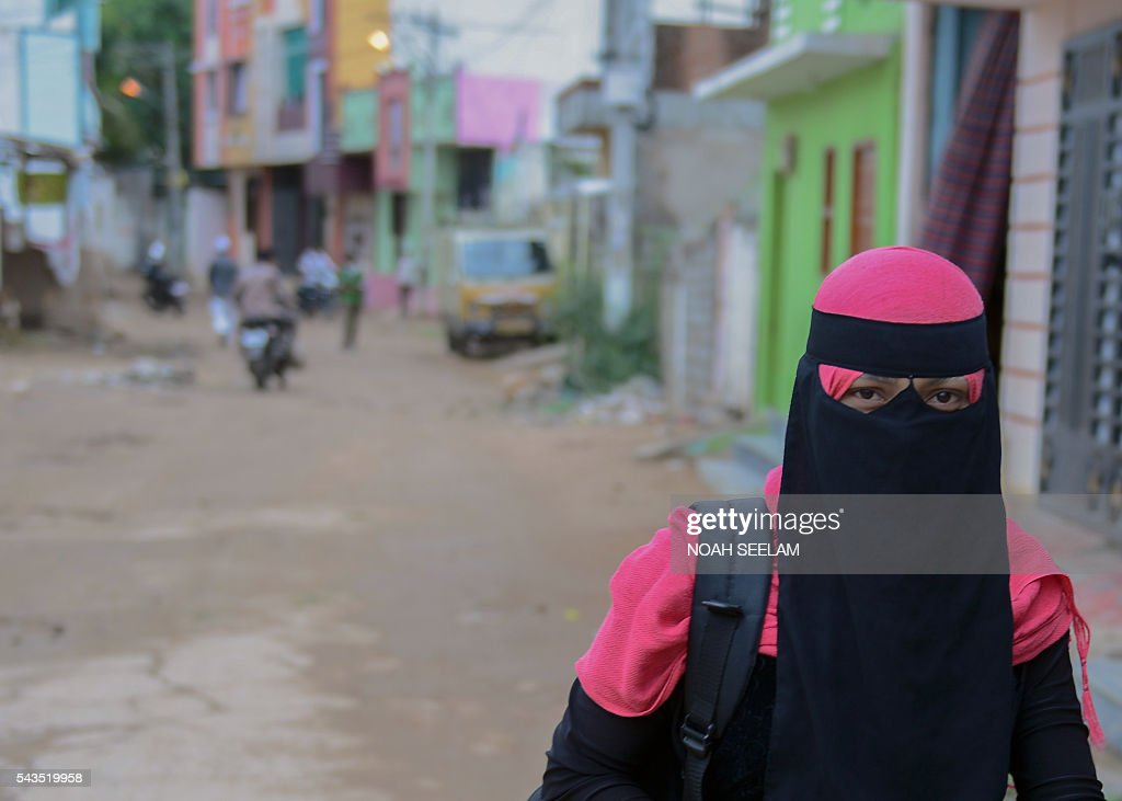 Rohingya Muslim woman Yasmeen walks to work from a refugee camp in the old city of Hyderabad on June 29, 2016. More than 1,200 Rohingya Muslims fleeing sectarian violence in Myanmar have settled in crammed quarters and makeshift shelters in the old city in Hyderabad, in the southern Indian state of Telangana. The Rohingyas have been described by the United Nations as one of the world's most persecuted minorities. They have fled Myanmar in their thousands in recent years as hardline monks and Buddhist nationalists fiercely oppose moves to recognise them as an official minority and insist on calling them 'Bengalis' -- shorthand for illegal migrants from the border with Bangladesh. / AFP / NOAH