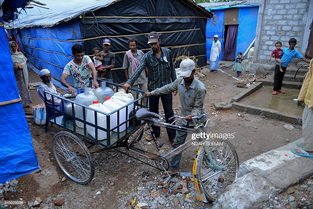 Rohingya Muslims bring drinking water cans in a tricycle to a refugee camp in the old city of Hyderabad on June 29, 2016. More than 1,200 Rohingya Muslims fleeing sectarian violence in Myanmar have settled in crammed quarters and makeshift shelters in the old city in Hyderabad, in the southern Indian state of Telangana. The Rohingyas have been described by the United Nations as one of the world's most persecuted minorities. They have fled Myanmar in their thousands in recent years as hardline monks and Buddhist nationalists fiercely oppose moves to recognise them as an official minority and insist on calling them 'Bengalis' -- shorthand for illegal migrants from the border with Bangladesh. / AFP / NOAH