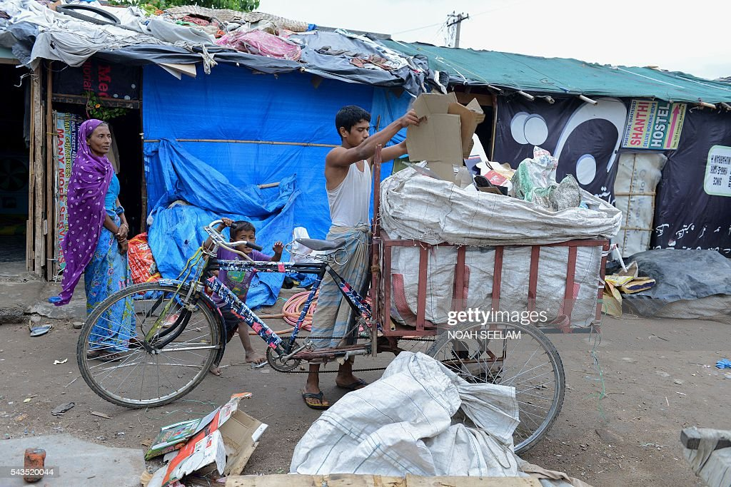 Rohingya Muslims sorts the scrap collected from a dump yard for their daily livelihood during the holy month of Ramadan in the old city of Hyderabad on June 29, 2016 Fleeing from sectarian violence and bloodshed in their country in 2012 between the Rohingya and Buddhist population, more than 1200 Rohingya Muslims have fled Myanmar and settled down in Hyderabad, the Southern Indian state of Telangana. These asylum seekers work as daily wagers and live crammed into cheap quarters.According to the United Nations, clashes between ethnic Rakhine Buddhists and Rohingya Muslims have left 115,000 people displaced and several dead. The Rohingyas have been described by the UN as one of the world's most persecuted minorities. . / AFP / NOAH