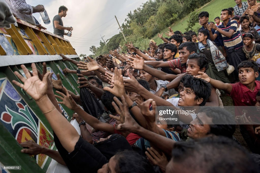 Rohingya people reach out to collect food and water rations at a newly set-up refugee camp at Balukhali in Cox's Bazar, Bangladesh, on Tuesday, Sept. 12, 2017. Myanmar's leader Aung San Suu Kyi is under attack over her response to a fresh round of violence that has seen more than 145,000 minority Rohingya Muslims flee into neighboring Bangladesh since last month. Photographer: Ismail Ferdous/Bloomberg via Getty Images