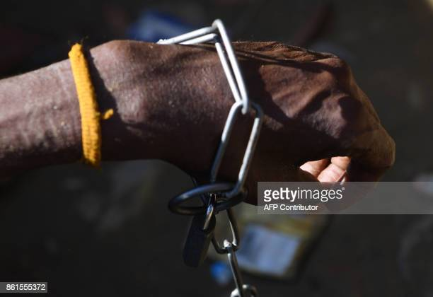 Rohingya refugee Ali Hussain is restrained by his sister with a metal chain at Balukhali refugee camp in the Bangladeshi district of Ukhia on October...