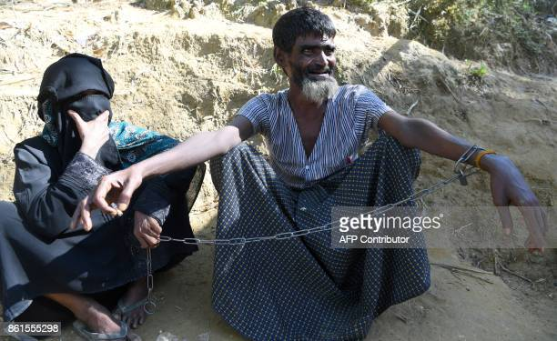 Rohingya refugee Ali Hussain looks on as he is restrained by his sister with a metal chain at Balukhali refugee camp in Ukhia district on October 15...