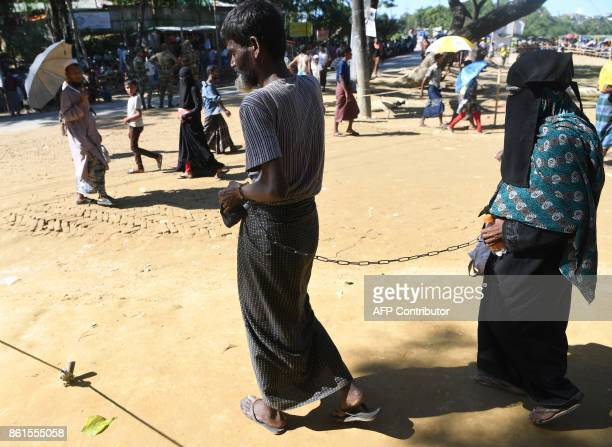 Rohingya refugee Ali Hussain walks as he is restrained by his sister with a metal chain at Balukhali refugee camp in the Bangladeshi district of...