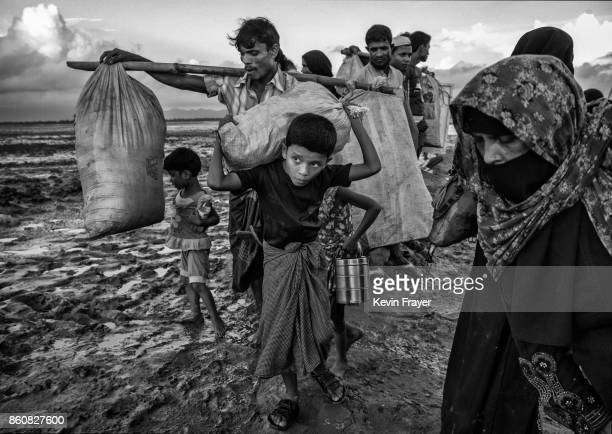 COX'S BAZAR BANGLADESH SEPTEMBER 21 A Rohingya refugee boy carries his belongings as he arrives with his family after crossing the Naf River at Shah...