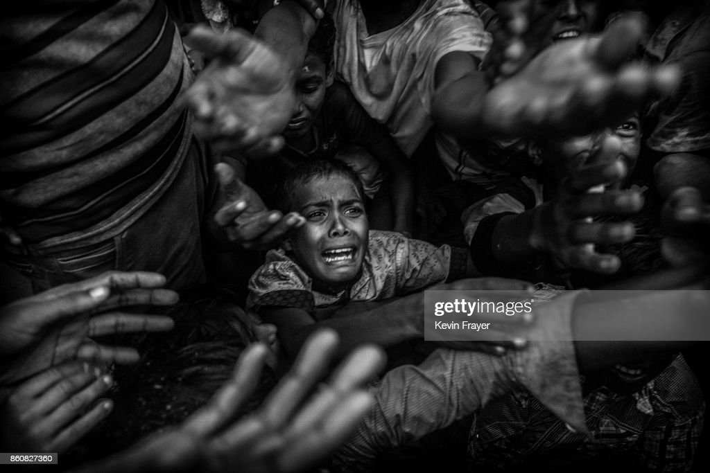 COX'S BAZAR, BANGLADESH - SEPTEMBER 18: A Rohingya refugee boy cries as he fights his way in the crowd to get food aid from a local NGO at the Balukali refugee camp on September 18, 2017 in Cox's Bazar, Bangladesh. More than half a million Rohingya refugees have flooded into Bangladesh to flee an offensive by Myanmar's military that the United Nations has called 'a textbook example of ethnic cleansing'. The refugee population is expected to swell further, with thousands more Rohingya Muslims said to be making the perilous journey on foot toward the border, or paying smugglers to take them across by water in wooden boats. Hundreds are known to have died trying to escape, and survivors arrive with horrifying accounts of villages burned, women raped, and scores killed in the 'clearance operations' by Myanmar's army and Buddhist mobs that were sparked by militant attacks on security posts in Rakhine state on August 25, 2017. What the Rohingya refugees flee to is a different kind of suffering in sprawling makeshift camps rife with fears of malnutrition, cholera, and other diseases. Aid organizations are struggling to keep pace with the scale of need and the staggering number of them - an estimated 60 percent - who are children arriving alone. Bangladesh, whose acceptance of the refugees has been praised by humanitarian officials for saving lives, has urged the creation of an internationally-recognized 'safe zone' where refugees can return, though Rohingya Muslims have long been persecuted in predominantly Buddhist Myanmar. World leaders are still debating how to confront the country and its de facto leader, Aung San Suu Kyi, a Nobel Peace Prize laureate who championed democracy, but now appears unable or unwilling to stop the army's brutal crackdown.