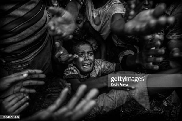 COX'S BAZAR BANGLADESH SEPTEMBER 18 A Rohingya refugee boy cries as he fights his way in the crowd to get food aid from a local NGO at the Balukali...
