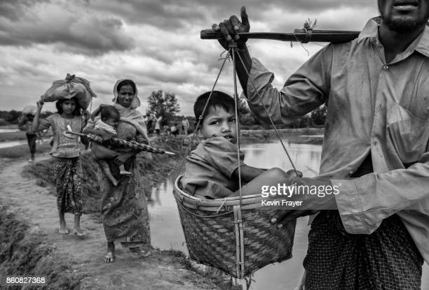 COX'S BAZAR BANGLADESH SEPTEMBER 24 A Rohingya refugee boy is carried in a basket by a relative after crossing the border on the Bangladesh side of...