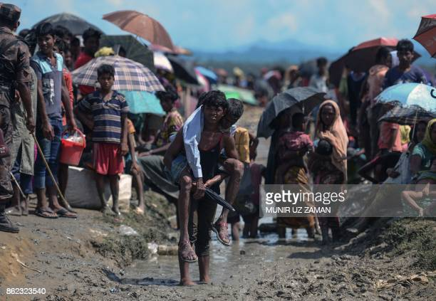 Rohingya refugee carries an old man in an area near no man's land on the Bangladesh side of the border with Myanmar after crossing the Naf River...
