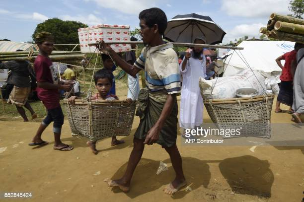 A Rohingya refugee carries his son and relief supplies in baskets at the Kutupalong refugee camp on September 24 2017 Nearly 430000 refugees have...
