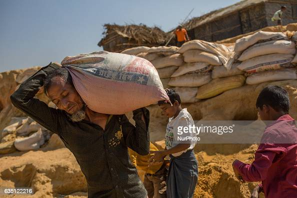A Rohingya refugee carries sand bag to build makeshift shelter at Kutupalong Refugee Camp Cox's Bazar Bangladesh on February 13 2017 After attacks by...