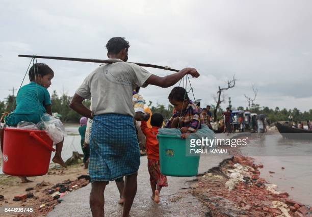 Rohingya refugee carries two children in buckets as they arrive in Bangladesh at Shah Porir Dwip in Teknaf on September 9 as they flee violence in...