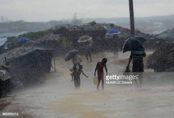 Rohingya refugee child carrries water during rain in a refugee camp at Kutupalong refugee camp in Bangladesh's Ukhia district on on October 12 2017...