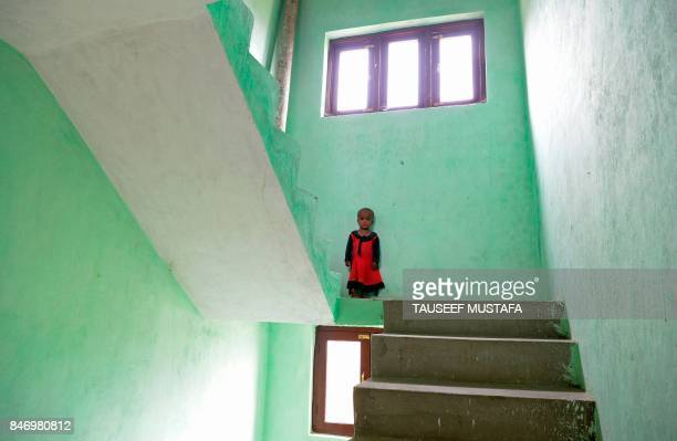 Rohingya refugee child poses in the stairwell of a building on the outskirts of Srinagar on September 14 2017 Eighteen families of Rohingya refugees...