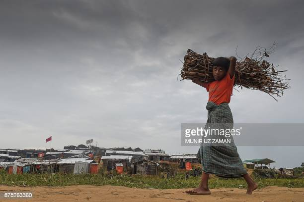 Rohingya refugee child walks back to his house with a bundle of dry wood at Thankhali refugee camp in the Bangladeshi district of Ukhia on November...