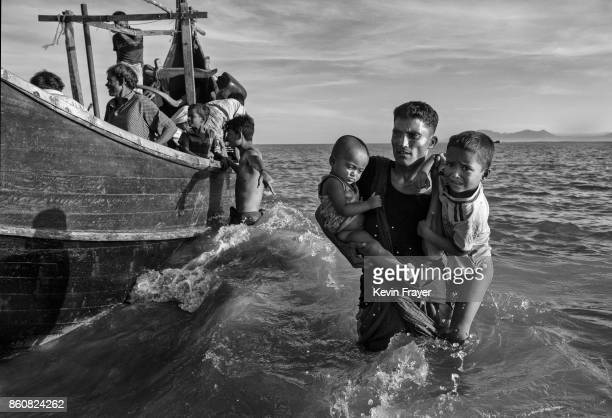 COX'S BAZAR BANGLADESH OCTOBER 01 Rohingya refugee children are carried from a boat at a beach on the Bangladesh side of the Naf River at Shah Porir...