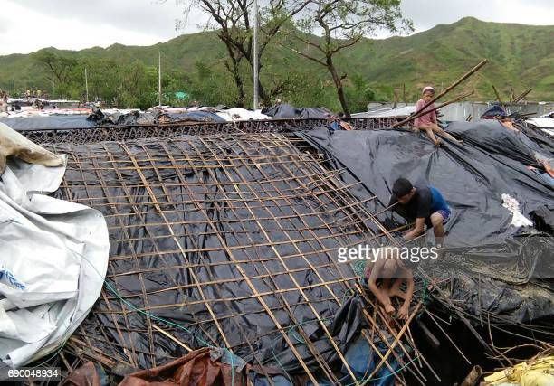Rohingya refugee children fix the damaged roof of a hut in a makeshift camp in Bangladesh's Cox's Bazar district on May 30 2017 after Cyclone Mora...