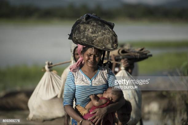 TOPSHOT Rohingya refugee cries as she walks after crossing the Naf river from Myanmar into Bangladesh in Whaikhyang on October 9 2017 A top UN...