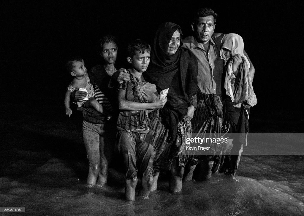 COX'S BAZAR, BANGLADESH - SEPTEMBER 26: A Rohingya refugee family reacts as they disembark from a boat after arriving on the Bangladesh side of the Naf River at night from Myanmar on September 26, 2017 in Cox's Bazar, Bangladesh. More than half a million Rohingya refugees have flooded into Bangladesh to flee an offensive by Myanmar's military that the United Nations has called 'a textbook example of ethnic cleansing'. The refugee population is expected to swell further, with thousands more Rohingya Muslims said to be making the perilous journey on foot toward the border, or paying smugglers to take them across by water in wooden boats. Hundreds are known to have died trying to escape, and survivors arrive with horrifying accounts of villages burned, women raped, and scores killed in the 'clearance operations' by Myanmar's army and Buddhist mobs that were sparked by militant attacks on security posts in Rakhine state on August 25, 2017. What the Rohingya refugees flee to is a different kind of suffering in sprawling makeshift camps rife with fears of malnutrition, cholera, and other diseases. Aid organizations are struggling to keep pace with the scale of need and the staggering number of them - an estimated 60 percent - who are children arriving alone. Bangladesh, whose acceptance of the refugees has been praised by humanitarian officials for saving lives, has urged the creation of an internationally-recognized 'safe zone' where refugees can return, though Rohingya Muslims have long been persecuted in predominantly Buddhist Myanmar. World leaders are still debating how to confront the country and its de facto leader, Aung San Suu Kyi, a Nobel Peace Prize laureate who championed democracy, but now appears unable or unwilling to stop the army's brutal crackdown.