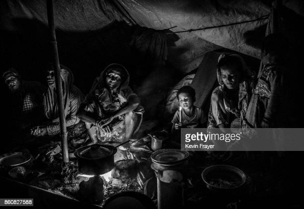 COX'S BAZAR BANGLADESH SEPTEMBER 18 A Rohingya refugee family uses a candle for light as they sit in a makeshift shelter on September 18 2017 on the...